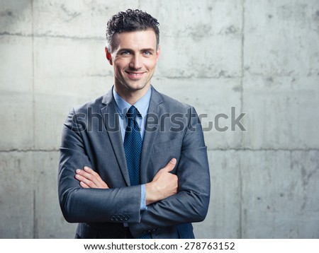 Portrait of a smiling handsome businessman with arms folded over concrete wall - stock photo