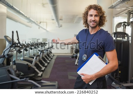 Portrait of a smiling handsome trainer with clipboard standing in the gym - stock photo