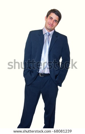 Portrait of a smiling handsome young businessman standing against isolated white background with hands in pockets