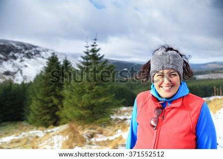Portrait of a smiling happy beautiful woman wearing colorful warm winter clothes standing in a snowy white mountain landscape in Ireland making a peace sign