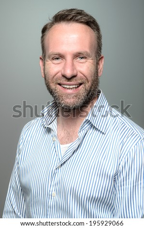 Portrait of a smiling happy handsome middle-aged man with a beard wearing a striped shirt looking at the camera with a warm friendly smile against a grey studio background