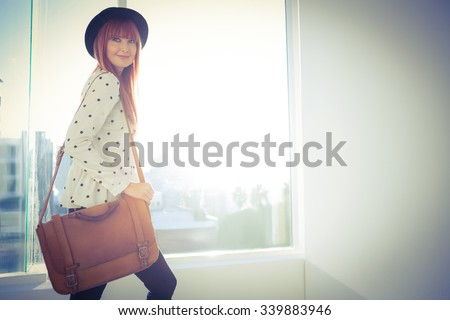 Portrait of a smiling hipster woman with a bag in a bright room - stock photo