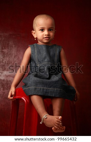 Portrait of a smiling Indian girl child in a red background - stock photo
