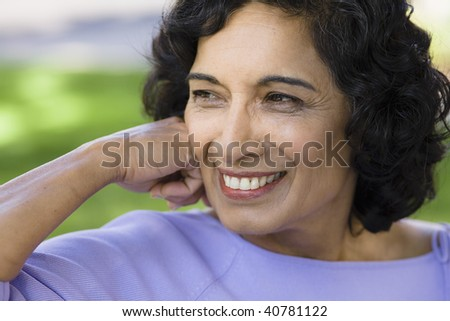 Portrait of a Smiling Indian Woman Sitting on a Bench in Park - stock photo