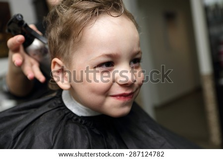 Portrait of a smiling kid at the barbershop - stock photo