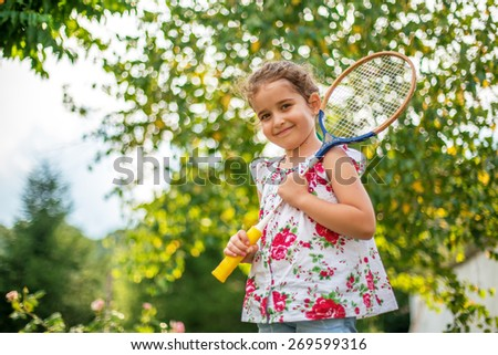 Portrait of a smiling little girl holding tennis Racket - stock photo