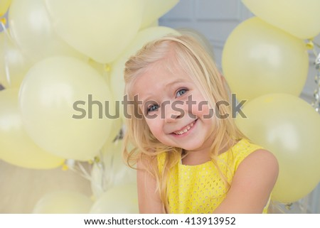 Portrait of a smiling little girl in a yellow dress with a yellow balloons - stock photo