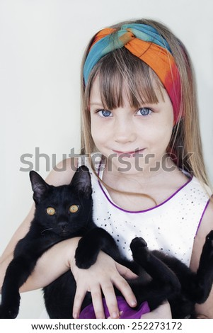 Portrait of a smiling little girl with black cat - stock photo