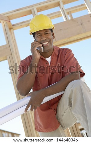 Portrait of a smiling male architect in hardhat with blueprints using cellphone at site - stock photo