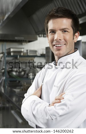 Portrait of a smiling male chef with arms crossed in kitchen