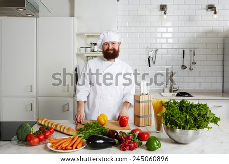 Portrait of a smiling male chef with fresh vegetables on big table standing in the kitchen - stock photo