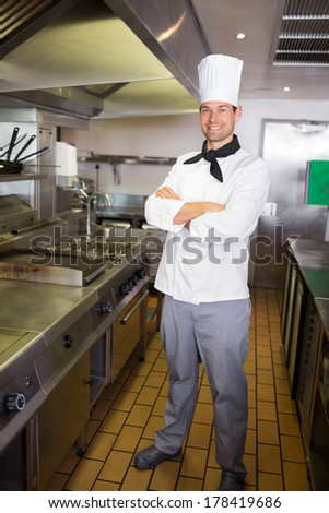 Portrait of a smiling male cook with arms crossed standing in the kitchen