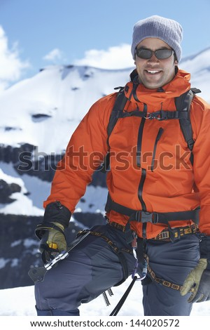 Portrait of a smiling male mountain climber standing against snowy mountains - stock photo