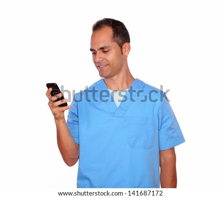 Portrait of a smiling male nurse sending message on cellphone on isolated background
