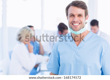 Portrait of a smiling male surgeon with colleagues in meeting at a medical office - stock photo