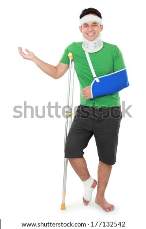 portrait of a smiling male with broken arm and foot using crutch presenting to copyspace isolated on white background - stock photo
