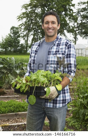 Portrait of a smiling man carrying plants in the field