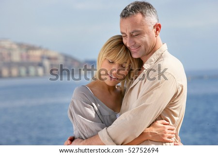 Portrait of a smiling man embracing a woman