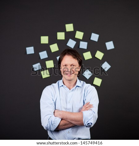 portrait of a smiling man in the middle of paper notes - stock photo