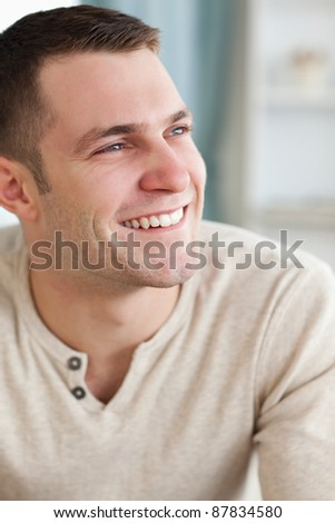 Portrait of a smiling man posing in his living room - stock photo