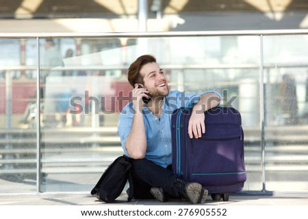 Portrait of a smiling man sitting with luggage and talking on mobile phone at airport - stock photo