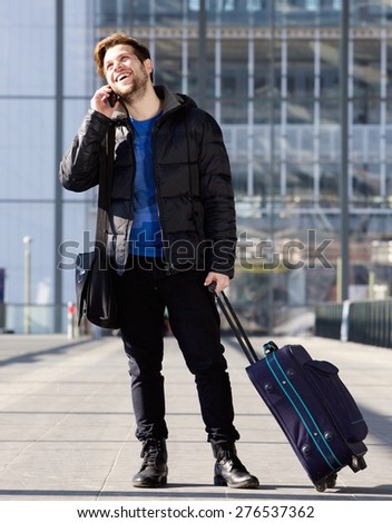 Portrait of a smiling man standing at station with bag talking on mobile phone - stock photo