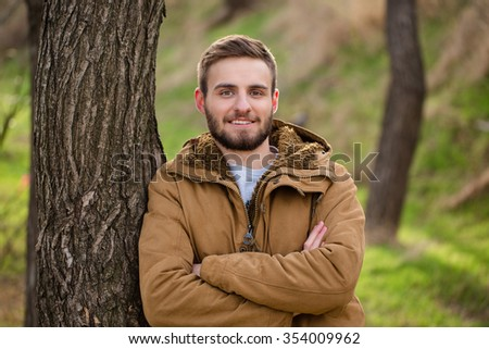 Portrait of a smiling man standing with arms folded outdoors and looking at camera - stock photo