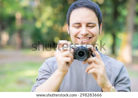 Portrait of a smiling man using a compact camera
