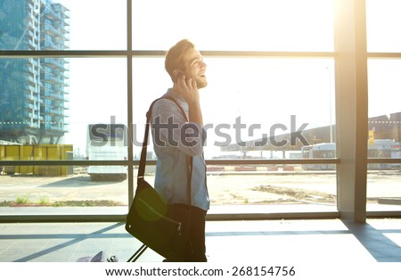 Portrait of a smiling man walking and talking on mobile phone at station - stock photo