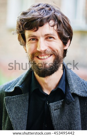 Portrait of a smiling man with a beard in a dark coat in the city closeup