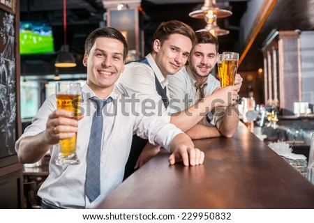 Portrait of a smiling man with a beer. Three cheerful friends met at the bar and clink glasses of beer while the bartender is standing on the bar. Friends having fun together - stock photo