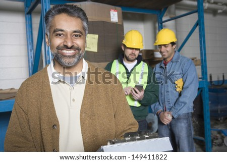 Portrait of a smiling man with colleagues in the background at factory - stock photo