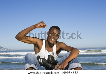 Portrait of a smiling man with football boots round neck cheering on beach - stock photo