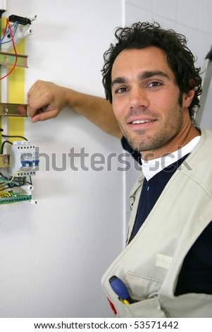 Portrait of a smiling man working on a circuit breaker - stock photo