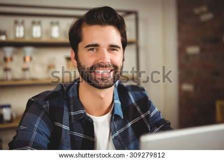 Portrait of a smiling man working on his laptop in a cafe - stock photo