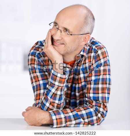 Portrait of a smiling mature balding caucasian man wearing glasses, sitting at a table, holding his chin with the hand and looking away in a daydreaming pensive mode - stock photo