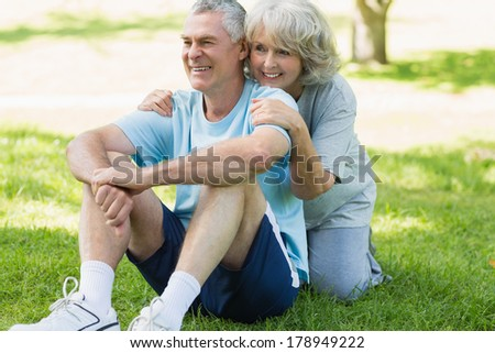 Portrait of a smiling mature couple sitting on grass at the park - stock photo