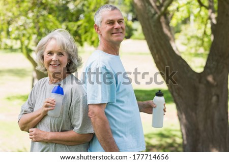 Portrait of a smiling mature couple standing with water bottles at the park