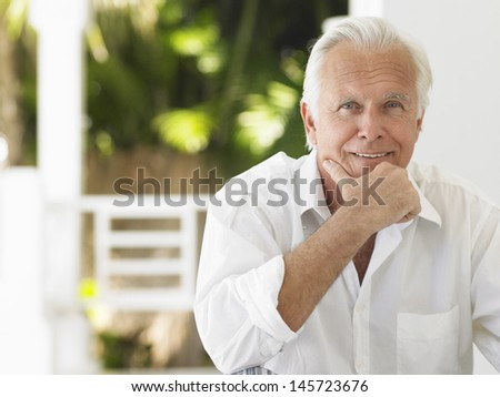 Portrait of a smiling mature man sitting on verandah - stock photo