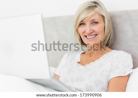 Portrait of a smiling mature woman using laptop in bed at home - stock photo