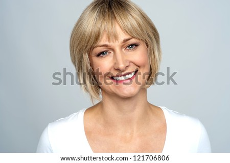Portrait of a smiling middle aged caucasian woman isolated against grey background. - stock photo