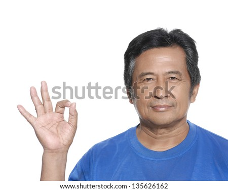 Portrait of a smiling middle aged man indicating OK sign against white - stock photo