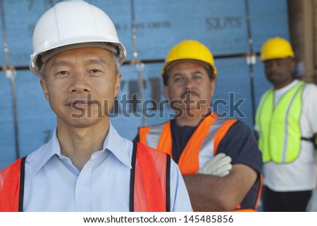 Portrait of a smiling middle-aged man with colleagues - stock photo