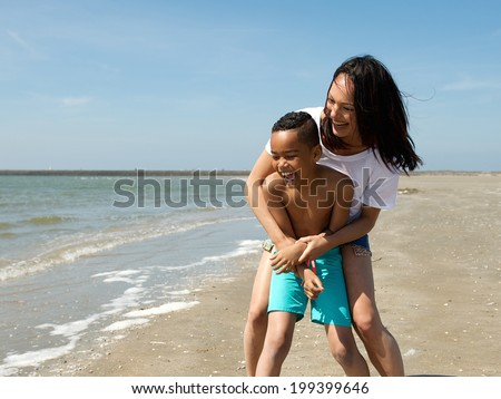 Portrait of a smiling mother and son playing at the beach  - stock photo