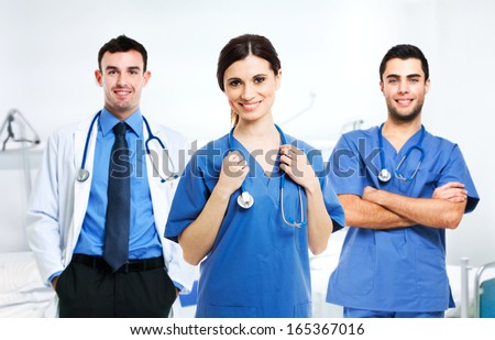 Portrait of a smiling nurse in front of her medical team - stock photo
