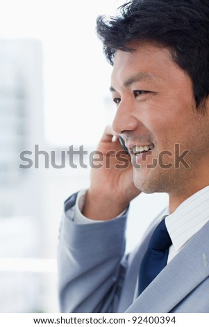 Portrait of a smiling office worker on the phone in his office