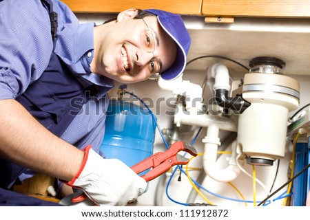 Portrait of a smiling plumber at work - stock photo