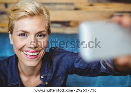 Portrait of a smiling pretty blonde talking a selfie
