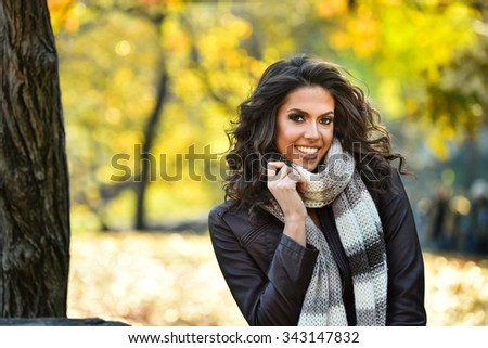 Portrait of a smiling pretty girl in the autumn park wearing leather jacket and scarf. - stock photo