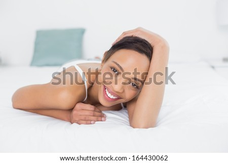 Portrait of a smiling pretty young woman relaxing in bed - stock photo
